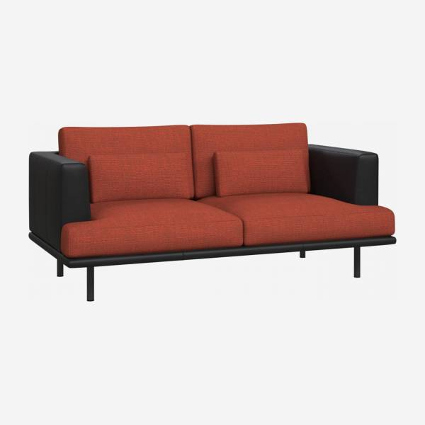 2 seater sofa in Fasoli fabric, warm red rock with base and armrests in black leather